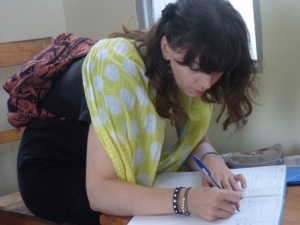 Maja Pecanac signs the visitors' reflections book on behalf of the GYC Delegation at the Bisesero Memorial in Karongi District, Rwanda